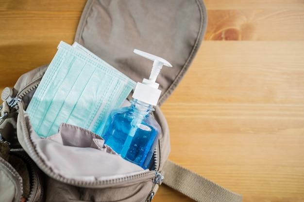 Concetto di nuovo o prossimo normale. maschera protettiva, gel alcolico nella borsa per proteggere quando si esce.