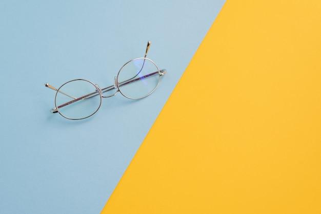 Concetto di occhiali da vista sullo scrittorio colorato normale di contrasto