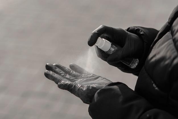 Concetto di pandemia del mondo coronavirus. mani femminili che spruzzano il liquido di disinfezione per proteggersi dall'infezione da virus.