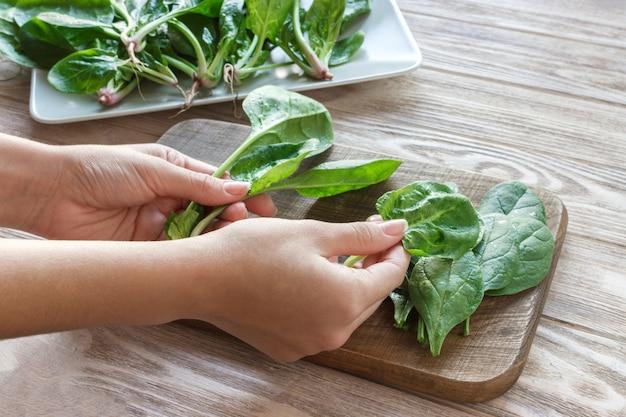 Concetto di panetteria vegetariana. le mani dello chef che tagliano gli spinaci in cucina del caffè, ristorante. avvicinamento