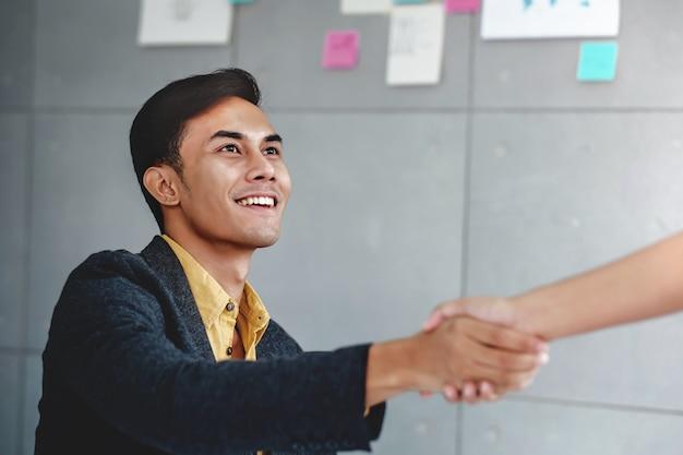 Concetto di partenariato giovane uomo d'affari felice nella sala riunioni dell'ufficio
