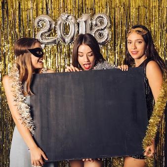 Concetto di partito di nuovo anno con tre ragazze e bordo