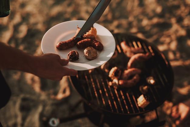 Concetto di partito. man grills barbecue sausages.