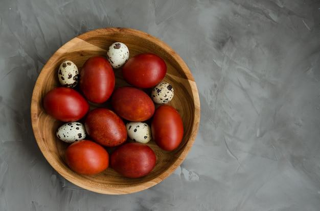 Concetto di pasqua. le uova di pasqua naturali in una ciotola di legno hanno cucinato in bucce di cipolla su un fondo di pietra scuro. orientamento orizzontale.
