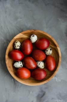 Concetto di pasqua. le uova di pasqua naturali in una ciotola di legno hanno cucinato in bucce di cipolla su un fondo di pietra scuro.