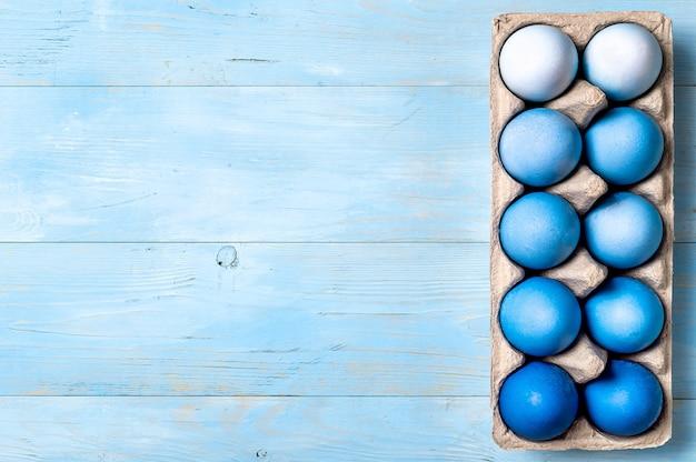 Concetto di pasqua. ombre eggs nei colori blu nell'imballaggio del cartone sul fondo di legno blu