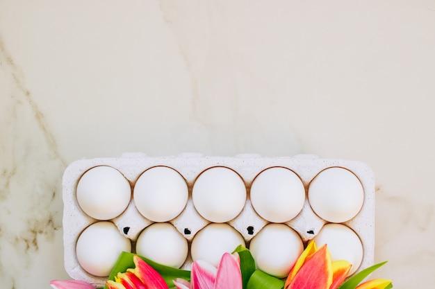 Concetto di pasqua, piatto posare le uova di pollo e tulipani colorati su fondo di marmo. vista dall'alto.
