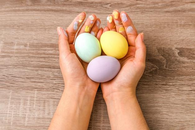 Concetto di pasqua. primo piano bella donna mani in possesso di tre uova colorate in teneri colori pastello giallo, menta e viola sul tavolo di legno