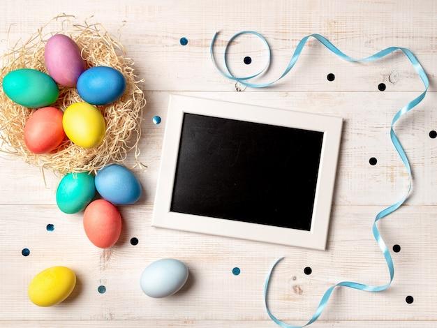 Concetto di pasqua. uova colorate su sfondo bianco in legno con lavagna vuota. copi lo spazio per i saluti, il testo o il disegno. vista dall'alto verso il basso o disteso