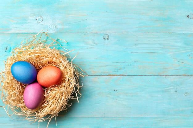 Concetto di pasqua. uova colorate su sfondo blu in legno con copia spazio per il testo. vista dall'alto verso il basso o disteso