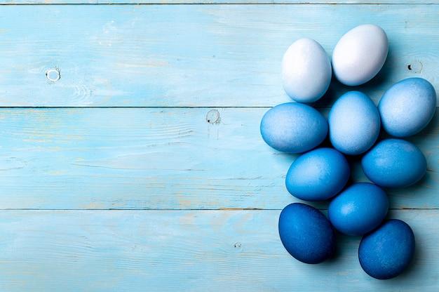 Concetto di pasqua. uova di ombre nei colori blu su fondo di legno blu