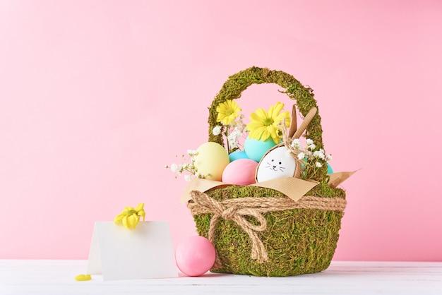 Concetto di pasqua. uova di pasqua in cestino decorativo con i fiori su un colore rosa