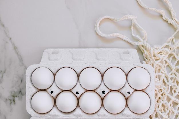 Concetto di pasqua, uova di pollo piatto e borsa eco su fondo di marmo. vista dall'alto.