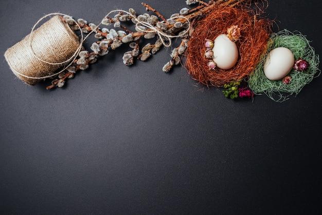 Concetto di pasqua, uova, rami di salice su sfondo nero.