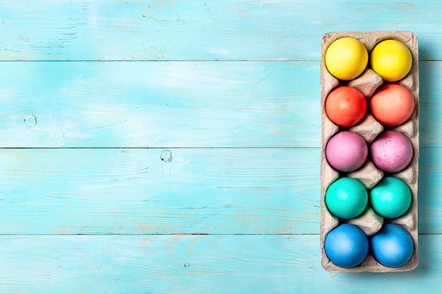 Concetto di pasqua. uova variopinte in cartone che imballa sul fondo di legno blu con lo spazio della copia per testo. vista dall'alto verso il basso o disteso