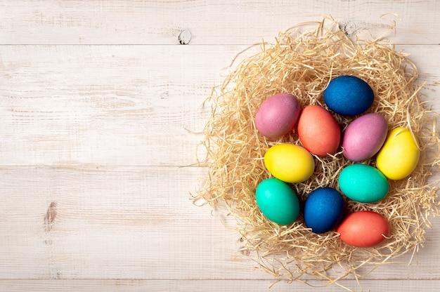 Concetto di pasqua. uova variopinte su fondo di legno bianco con lo spazio della copia per testo o progettazione. vista dall'alto verso il basso o disteso