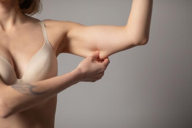 Concetto di perdita di peso. donna chubby che pizzica il grasso del braccio superiore isolato su gray.
