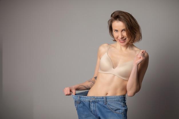 Concetto di perdita di peso. la giovane donna le mostra la perdita di peso e indossa i suoi vecchi jeans. donna esile in grandi jeans che mostrano come stava perdendo peso