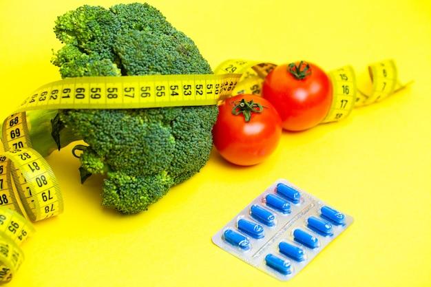 Concetto di perdita di peso, verdure con nastro adesivo di misurazione su giallo.