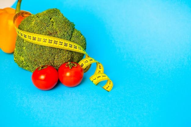 Concetto di perdita di peso, verdure con nastro adesivo di misurazione sul blu.