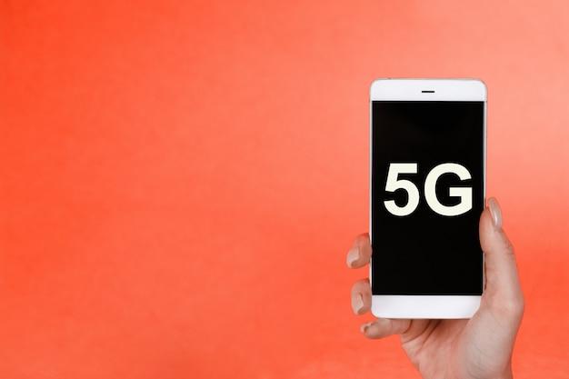 Concetto di pericolo, mano che tiene un telefono con un simbolo 5g. il concetto di rete 5g