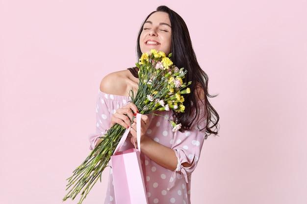 Concetto di persone, divertimento e felicità. donna dai capelli scuri positiva con capelli neri, abbraccia i fiori, porta una borsa regalo, posa in rosa chiaro. gioie femminili presenti l'8 marzo.