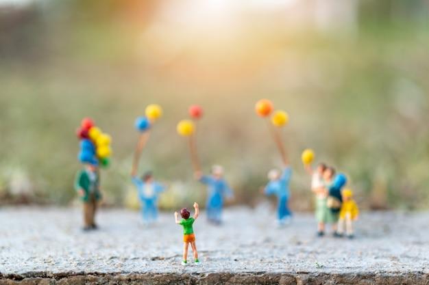 Concetto di persone in miniatura con famiglia felice con palloncini