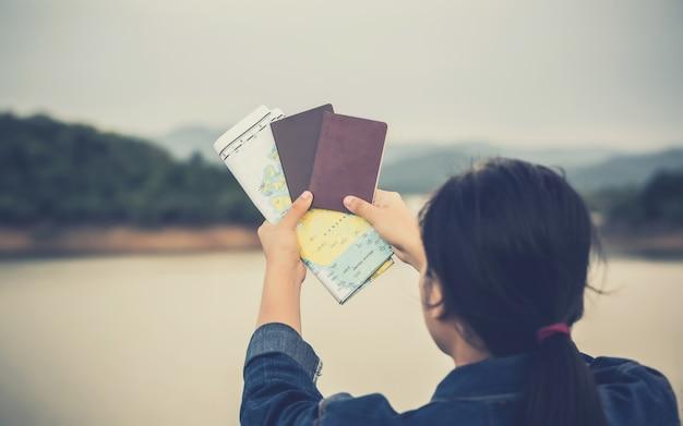Concetto di persone in viaggio. mano che mostra il passaporto sul cielo