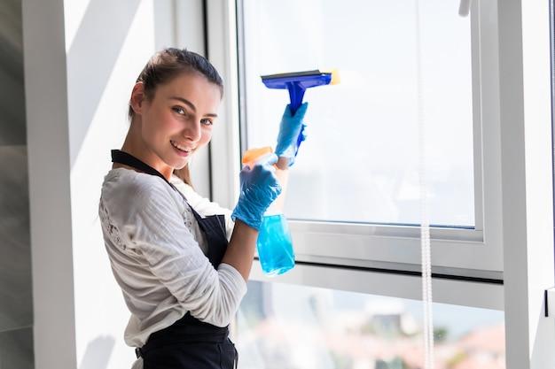 Concetto di persone, lavori domestici e pulizie. la donna felice in guanti che puliscono la finestra con lo straccio e la pulitrice spruzzano a casa