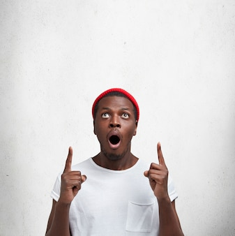 Concetto di persone, pubblicità ed etnia. il colpo verticale di un maschio dalla pelle scura stupito guarda verso l'alto e indica con le dita anteriori al soffitto, vede qualcosa di inaspettato