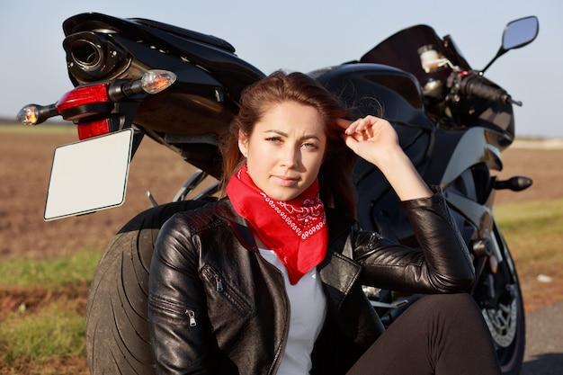Concetto di persone, riposo e hobby. la bella donna attiva indossa una bandana rossa, si siede sulla strada vicino al suo mezzo di trasporto preferito