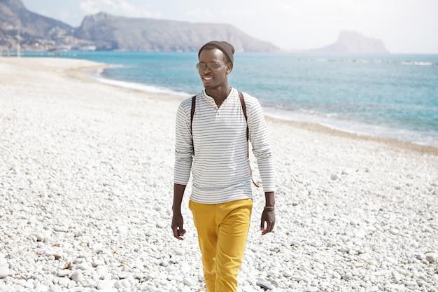 Concetto di persone, stile di vita, turismo, viaggi e vacanze. giovane viaggiatore con zaino e sacco a pelo maschio afroamericano allegro attraente che gode delle vacanze estive sulla spiaggia alla spiaggia
