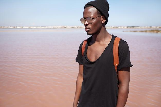 Concetto di persone, stile di vita, viaggi e moda. modello maschio afroamericano giovane alla moda attraente che indossa t-shirt nera a collo basso, cappello e lenti con lenti a specchio in posa all'aperto in riva al mare