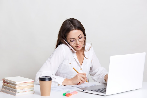 Concetto di persone, tecnologia e business. l'immagine della donna lavoratrice ha una conversazione telefonica, annota alcune note in taccuino, cerca informazioni sul computer portatile, beve il caffè, isolato su bianco