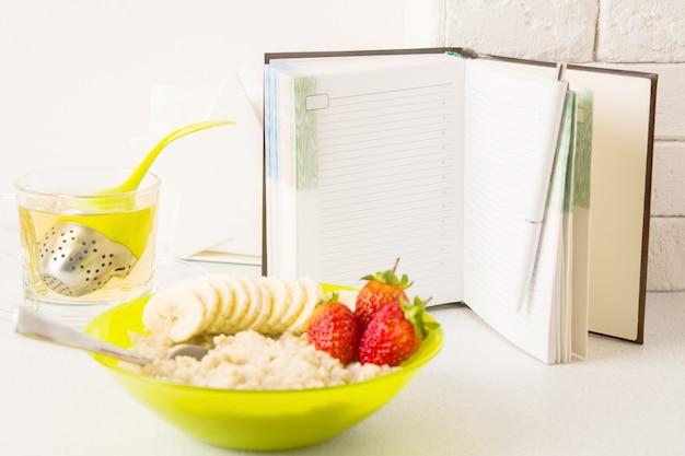 Concetto di pianificazione di dieta sana con il taccuino aperto a fuoco e piatto di porridge