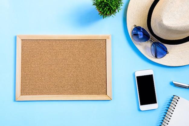 Concetto di pianificazione di viaggio di estate di vista superiore con il cappello bianco, gli occhiali blu, il telefono, il taccuino ed il bordo di legno marrone isolati