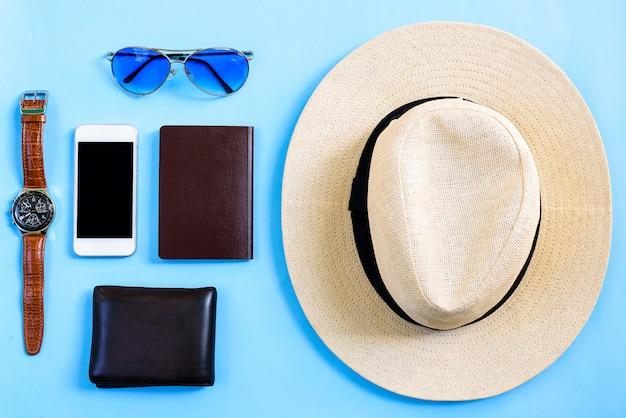 Concetto di pianificazione di viaggio di estate di vista superiore con il cappello bianco, gli occhiali blu, il telefono, l'orologio, il passaporto in bianco ed il portafoglio marrone isolati