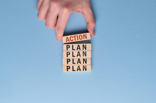 Concetto di piano di attivazione - la mano tiene il blocco di legno con l'iscrizione su uno spazio blu.
