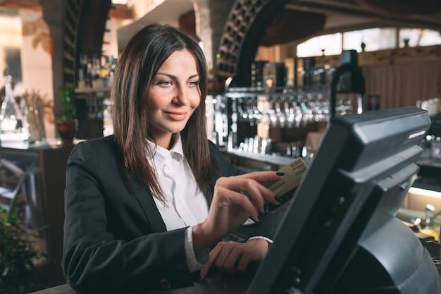 Concetto di piccola impresa, della gente e di servizio - donna o cameriere o responsabile felice in grembiule al contatore con la cassa che lavora al bar o alla caffetteria