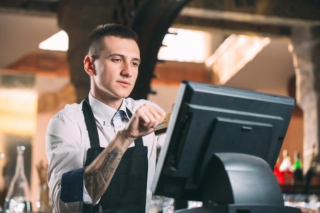 Concetto di piccola impresa, della gente e di servizio - uomo o cameriere felice in grembiule al contatore con la cassa che funziona alla barra o alla caffetteria
