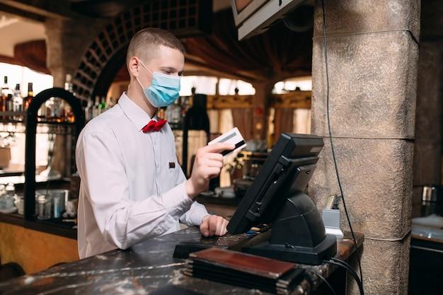 Concetto di piccole imprese, persone e servizi. uomo o cameriere in maschera medica al bancone con cassa lavorando al bar o alla caffetteria.