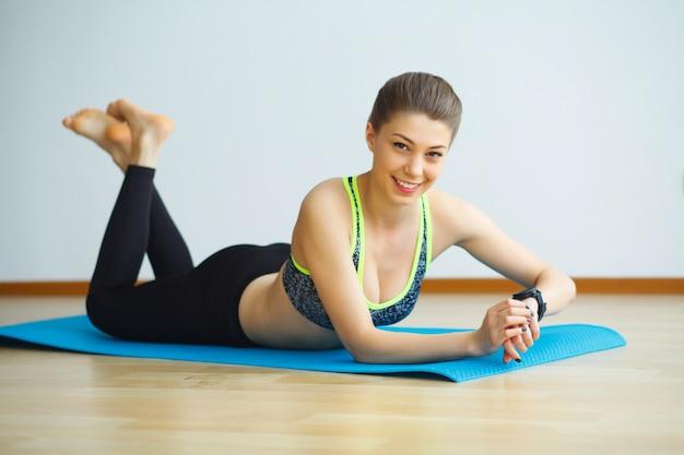 Concetto di pratica di yoga della giovane donna attraente dei yogi, indossando abiti sportivi, canottiera sportiva e pantaloni neri, integrale