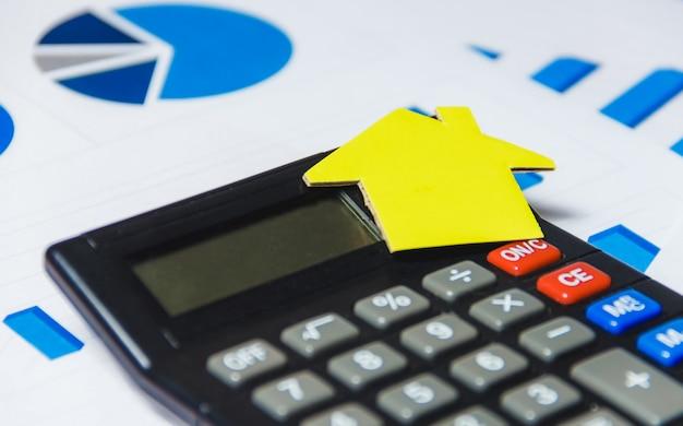 Concetto di prestiti ipotecari con la camera e il calcolatore di carta su fondo bianco
