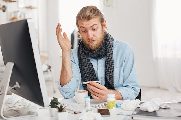 Concetto di problemi di salute. stupito giovane impiegato con la barba ha un brutto raffreddore, influenza, guarda il termometro con gli occhi incavati dopo aver misurato la temperatura corporea. manager malato su sfondo ufficio