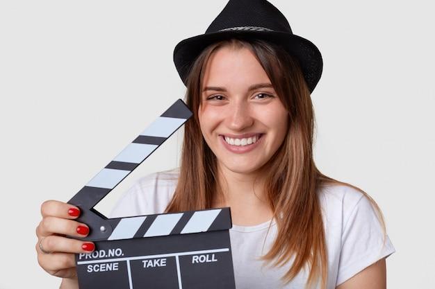 Concetto di produzione cinematografica. la donna allegra dall'aspetto piacevole indossa un cappello, ha un ampio sorriso, tiene l'ardesia del film o il ciak, essendo di buon umore, passa il tempo sul set del film, isolato sul muro bianco