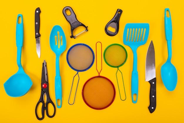 Concetto di progetto degli utensili della cucina isolati su giallo