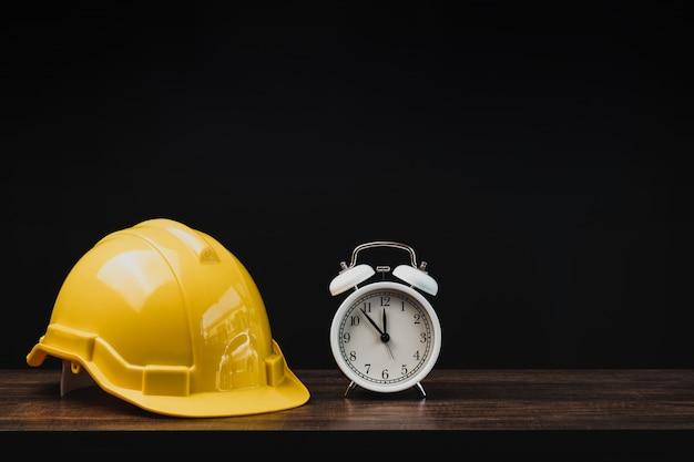Concetto di progetto del bene immobile, della proprietà e di costruzione, strumenti dell'ingegnere con il casco sulla tavola nel fondo scuro
