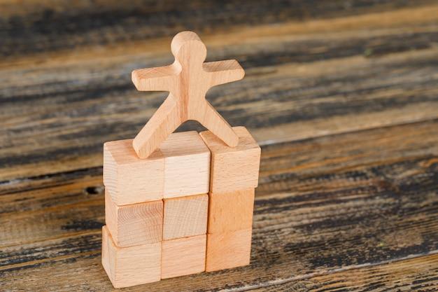 Concetto di promozione di carriera e di affari con il modello umano sui cubi di legno sulla vista di angolo alto della tavola di legno.
