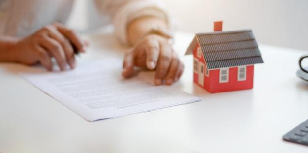 Concetto di proprietà immobiliare: contratto di firma del cliente sull'accordo di mutuo per la casa