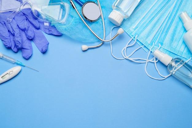 Concetto di protezione del coronavirus - guanti in lattice, maschera, siringa disinfettante per le mani, stetoscopio e termometro su sfondo blu